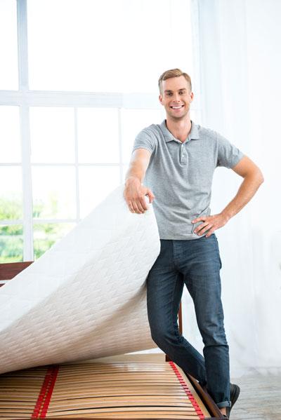 man recycling used mattress